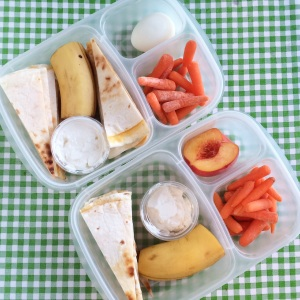 Quesadilla with sour cream for dipping, banana, carrots.  He has a boiled egg, she has a half a peach.