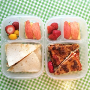 She has quesadilla, apples, tomatoes and strawberries.  He has leftover homemade pizza, cheese, apples and strawberries.  Whenever I make things like pizza and quesadilla, I always make extra.  It's super easy to pack a lunch when the main item is already made in the fridge.
