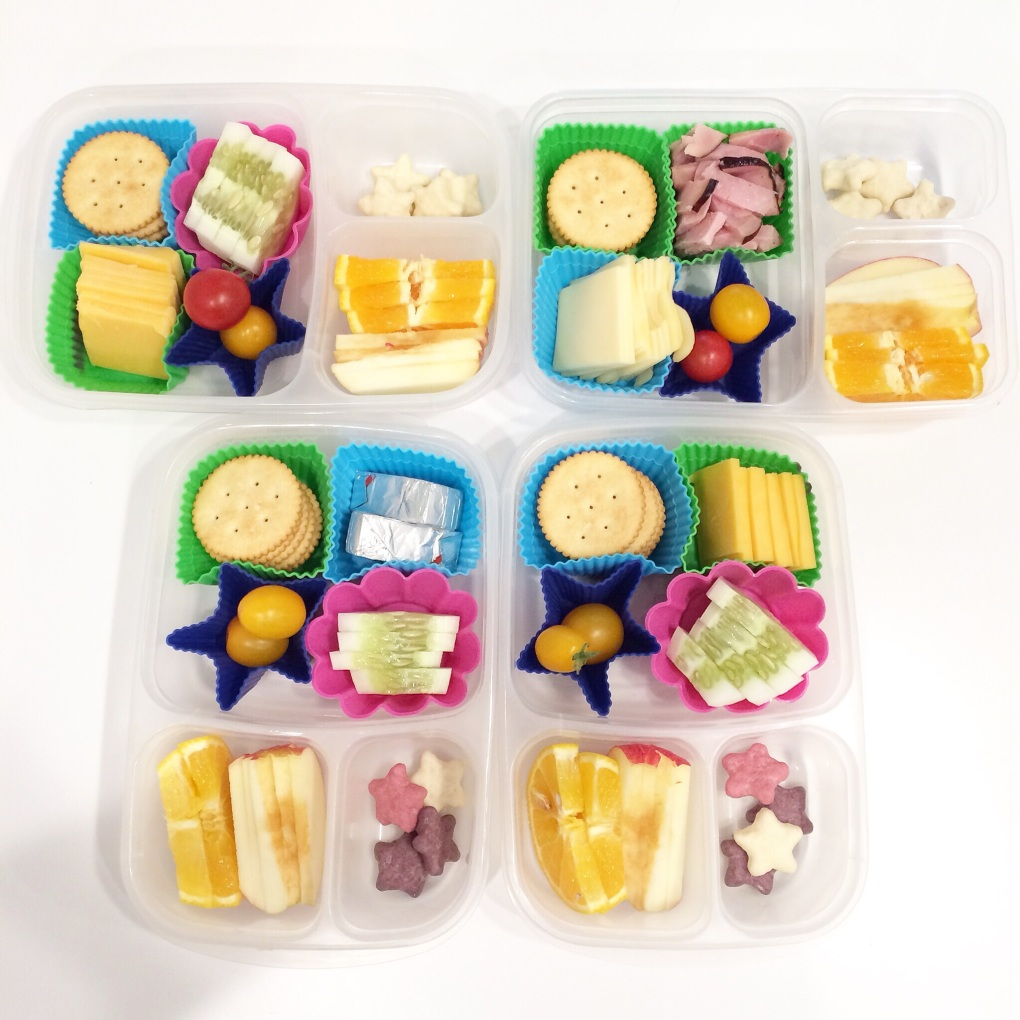 My version of a lunchable.  Crackers (Trader Joe's version of a Ritz style cracker), tomatoes, apples, oranges, cheese.  The three girls have slices of cucumber from our garden, the boy has some bites of Applegate ham.  And a few yogurt covered star cookies for everyone.